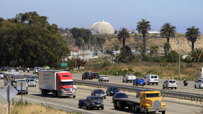 In this Thursday, June 30, 2011 picture, a steady flow of traffic on Interstate 5 runs past the San Onofre Nuclear Generating Station in San Clemente, Calif. A new government report to be released Wednesday, April 10, 2013 challenges a pillar of planning for disasters at American nuclear power plants, finding that people living beyond the official 10-mile evacuation zone might be so frightened by the prospect of spreading radiation that they would flee of their own accord, clog roads, and delay the escape of others.  (AP Photo/Lenny Ignelzi)