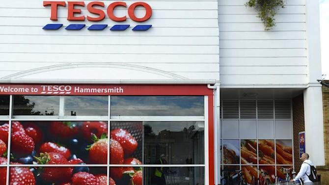 A man pushes his shopping trolley into a Tesco store in Hammersmith, west London