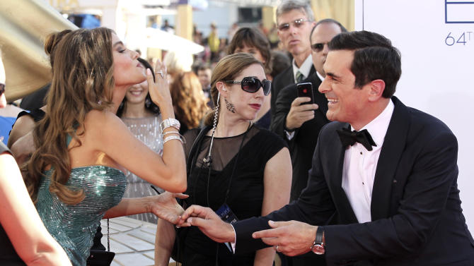 """Sofia Vergara, left, and Ty Burrell, right, of """"Modern Family"""" arrive at the 64th Primetime Emmy Awards at the Nokia Theatre on Sunday, Sept. 23, 2012, in Los Angeles. (Photo by Matt Sayles/Invision/AP)"""