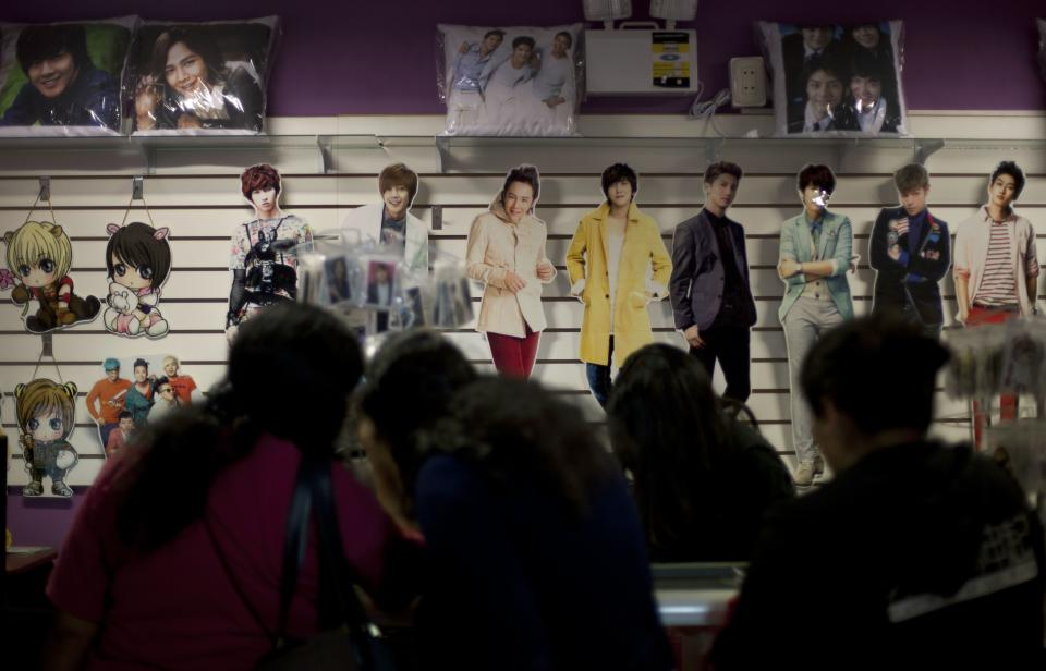 In this May 25, 2013 photo, followers of K-pop music look at souvenirs of singers inside a store at the Arenales shopping center in Lima, Peru. The Arenales shopping center has entire floors dedicated to South Korean music, clothes and food. (AP Photo/Martin Mejia)