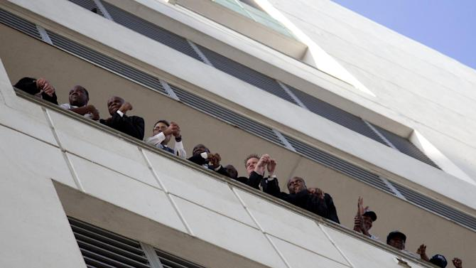 People look out from a balcony at the Westin Diplomat Hotel where President Barack Obama is attending a campaign event, Tuesday, April 10, 2012, in Hollywood, Fla. (AP Photo/Carolyn Kaster)