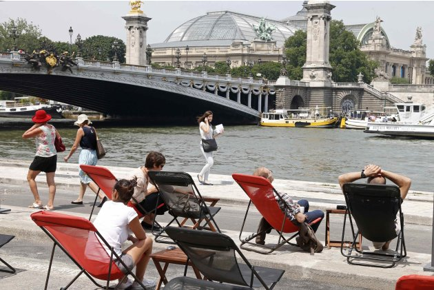 People relax on deck chairs at a cafe terrace on the opening day of the new pedestrian walkway area between Orsay museum and Alma bridge on the left bank of the River Seine in Paris