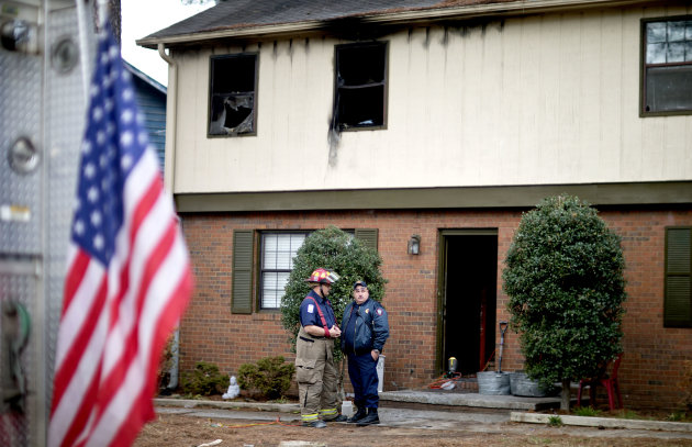 Rockdale County fire officials stand outside the scene of a house fire that killed four children, including an infant, Wednesday, Jan. 9, 2013, in Conyers, Ga.The fire burned late Tuesday night at a duplex in Conyers, east of Atlanta. Another child, who is 6, was thrown by his mother from a second-floor window, said Glenn Allen, a spokesman for Georgia's fire commissioner. The child injured his shoulder in the fall but survived. The mother was taken to Grady Memorial Hospital in Atlanta with second- and third-degree burns, Allen said. (AP Photo/David Goldman)