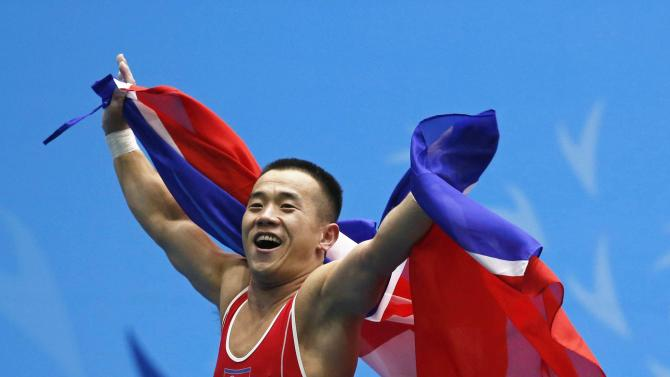 North Korea's Om reacts on stage after winning the men's 56kg  weightlifting competition at the Moonlight Festival Garden during the 17th Asian Games in Incheon