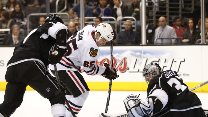 Chicago Blackhawks' Andrew Shaw, center, works against Los Angeles Kings' Alec Martinez, left, as he tries to score against Kings goalie Jonathan Quick during the first period of an NHL hockey game in Los Angeles, Saturday, Jan. 19, 2013. (AP Photo/Jae C. Hong)