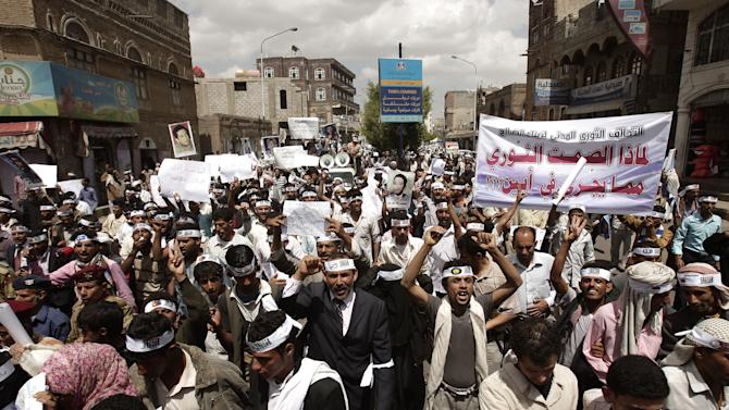 "FILE - In this April 23, 2012, file photo Yemeni members of the Peaceful Revolution Salvation Front chant slogans during a demonstration demanding independence of the judicial system from government control in Sanaa, Yemen. Yemen's al-Qaida of the Arabian Peninsula (AQAP) is becoming a major draw for foreign fighters as it carves out a stronghold in the south of the country, easily defeating Yemeni forces preoccupied battling tribal and political unrest. Arabic on the banner reads, ""Why the revolutionary silence toward what's happening in Abian"", referring to army action against al-Qaida in that area. (AP Photo/Hani Mohammed, File)"