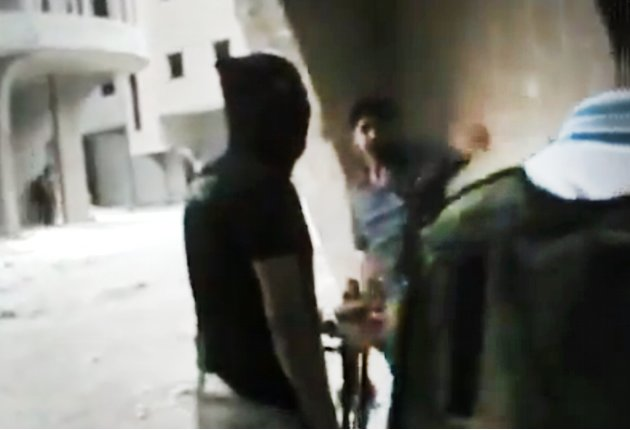 This image made from amateur video released by the Ugarit News and accessed Sunday, July 15, 2012, purports to show Free Syrian Army soldiers during clashes with Syrian government forces in Damascus,