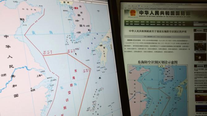 "Computer screens display a map showing the outline of China's new air defense zone in the East China on the website of the Chinese Ministry of Defense, in Beijing Tuesday, Nov. 26, 2013. Beijing on Saturday, Nov. 23, 2013 issued a map of the zone - which includes a cluster of islands controlled by Japan but also claimed by China - and a set of rules that say all aircraft entering the area must notify Chinese authorities and are subject to emergency military measures if they do not identify themselves or obey Beijing's orders. Chinese characters in red in the center of the map at left reads: ""Air Defense Identification Zone in East China Sea."" (AP Photo/Ng Han Guan)"