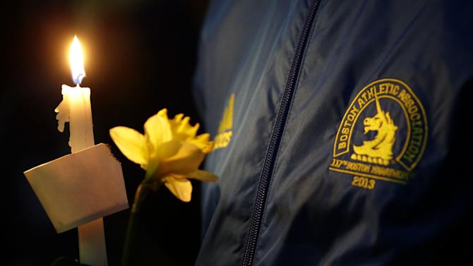 Lizzie Lee, 56, of Lynwood, Wash., who was participating in her first Boston Marathon and 11th overall, holds a candle and a flower at Boston Common during a vigil for the victims of the Boston Marathon explosions, Tuesday, April 16, 2013, one day after bombs exploded at the finish line of the Boston Marathon. (AP Photo/Julio Cortez)