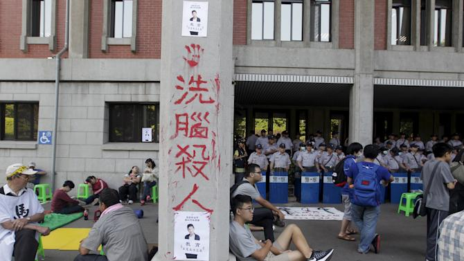 Police officers stand guard as students protest at the entrance to the Ministry of Education in Taipei