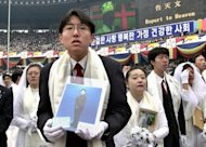 File photo taken in 2000 shows newly weds, some holding portraits of partners who couldn&#39;t attend, listening to Unification Church founder Sun Myung Moon preach during a mass wedding ceremony in Seoul. The church claims a worldwide following of three million