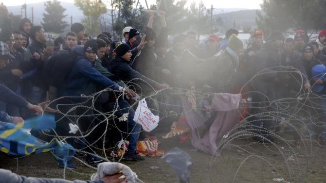 Migrants pull the barbed wire as they try to cross the Greek-Macedonian border near the Greek village of Idomeni