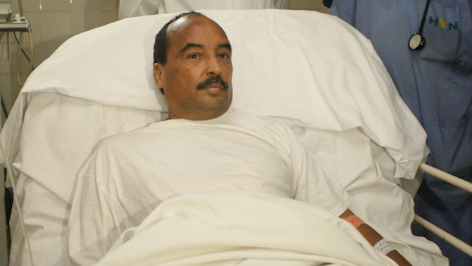 File - In this Sunday, Oct. 14, 2012, handout file photo released by the Mauritanian government news agency AMI (Agence Mauritanienne de l'Information), Mauritanian President Mohamed Ould Abdel Aziz recovers at the Ksar Military Hospital in Noukchott, Mauritania before being evacuated to France for further treatment for a gunshot wound sustained to the arm. Mauritania's Minister of Communication says President Mohamed Ould Abdel Aziz has been lightly wounded by friendly fire after his vehicle was fired upon by the military on the outskirts of the capital, Nouakchott. Thousands of Mauritanians lined the street from the airport to welcome back President Mohamed Ould Abdel Aziz, who went to France for five weeks of medical treatment after being accidentally shot in a friendly fire incident. His return Saturday Nov 24 2012, puts an end to speculation over the state of his health, as well as over the future of Mauritania.(AP Photo/Agence Mauritanienne de l'Information, file)