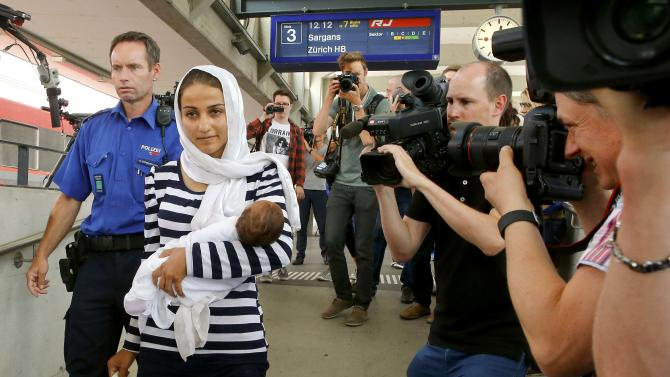 Media surround migrant from Syria upon her arrival at the railway station in the north-eastern Swiss town of Buchs