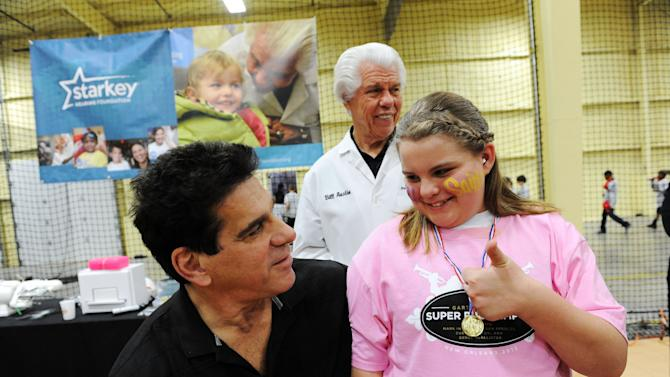 IMAGE DISTRIBUTED FOR STARKEY HEARING FOUNDATION - The Incredible Hulk actor Lou Ferrigno talks to a young girl after Bill Austin (center), founder of Starkey Hearing Foundation, fits her with a hearing aid at The Citi Garth Brooks Super Pro Camp on Friday, Feb. 1, 2013 in New Orleans. (Photo by Cheryl Gerber/Invision for Starkey Hearing Foundation/AP Images)