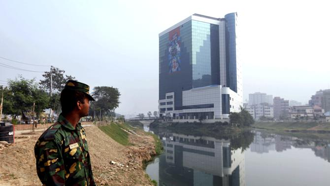 "In this Saturday, Dec. 8, 2012, photo, a Bangladesh Army soldier stands near the headquarters of the Bangladesh Garment Manufacturers and Export Association (BGMEA) in Dhaka, Bangladesh. About a year before a November fire at a clothing factory in Bangladesh killed 112 people, executives from Wal-Mart, Gap and other big clothing companies met nearby in the country's capital to discuss a legally binding contract that would govern safety inspections. But after a spokeswoman for Wal-Mart, the world's largest retailer, got up and said the proposal wasn't ""financially feasible,"" the effort quickly lost momentum. (AP Photo/A.M. Ahad)"