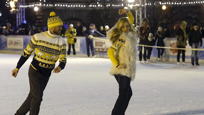 Russian figure skaters Navka and Kostomarov perform at ice rink on first day of operation in front of GUM department store in Moscow's Red Square