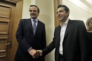 Alexis Tsipras, leader of the Coalition of the Radical Left party, SYRIZA, (R) shakes hands with Antonis Samaras, leader of the Conservative &#39;New Democracy&#39; party, before their meeting at the Greek Parliament in Athens