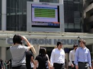 "People walk near a digital screen displaying stocks in the financial district of Singapore. Formula One is set to be one of the biggest IPOs this year. The latest comments come just a day after Graff Diamonds postponed its $1.0 billion launch in Hong Kong due to ""adverse market conditions"""