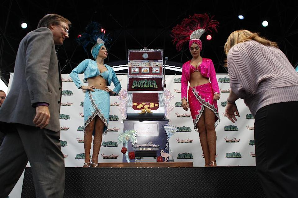 Showgirls and others stand beside Slotzilla during a press conference in Las Vegas Tuesday, Nov. 27, 2012. Slotzilla is a permanent zipline attraction planned for downtown Las Vegas. (AP Photo/Las Vegas Review-Journal, John Locher)