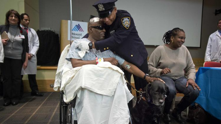 Blind man Cecil Williams pets his service dog Orlando as he is hugged by police officer Anthony Duncan following a press conference in New York