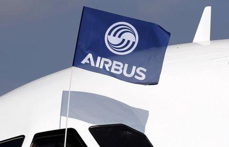 A flight test engineer holds an Airbus Group flag after the first flight of the Airbus A320neo in Colomiers near Toulouse