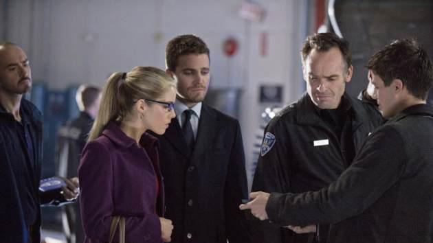 Emily Bett Rickards as Felicity Smoak, Stephen Amell as Oliver Queen, Paul Blackthorne as Quentin Lance, and Grant Gustin as Barry Allen in 'The Scientist' episode of 'Arrow' -- The CW