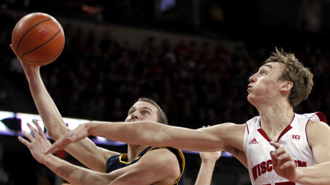Michigan's Nik Stauskas, left, shoots as Wisconsin's Sam Dekker defends during the first half of an NCAA college basketball game Saturday, Feb. 9, 2013, in Madison, Wis. (AP Photo/Andy Manis)
