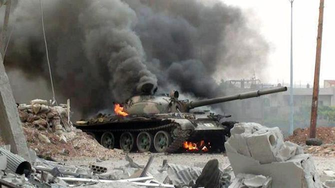 This citizen journalism image provided by The Syrian Revolution against Bashar Assad which has been authenticated based on its contents and other AP reporting, shows a Syrian military tank on fire during clashes with Free Syrian army fighters in Joubar, a suburb of Damascus, Syria, Wednesday, Sept. 18, 2013. (AP Photo/The Syrian Revolution Against Bashar Assad)