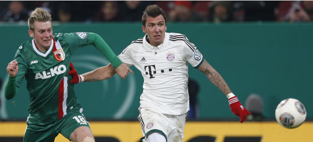 Augsburg's Jan-Ingwer Callsen-Bracker, left, and Bayern's Mario Mandzukic of Croatia challenge for the ball during the German soccer cup third round match between FC Augsburg and FC Bayern Mun
