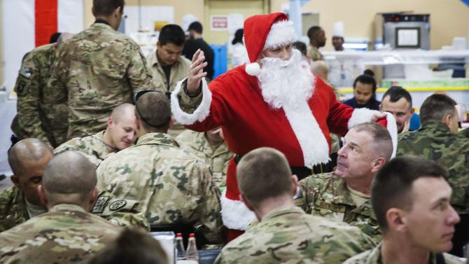 A U.S. soldier from the 3rd Cavalry Regiment dressed as Santa Claus greets fellow soldiers eating a Christmas day lunch on forward operating base Gamberi in the Laghman province of Afghanistan