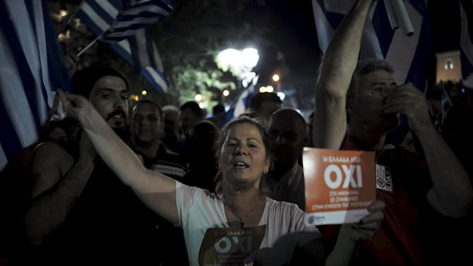 """""""No"""" supporters shout slogans and wave Greek national flags during celebrations following a referendum in Athens, Greece"""