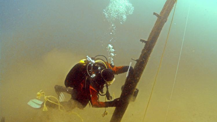 In this June 16, 2013 file photo provided by Great Lakes Exploration Group, diver Jim Nowka of Great Lakes Exploration Group inspects a wooden beam extending from the floor of Lake Michigan that experts believe may be part of the Griffin, a ship that sank in 1679. A wooden beam that has long been the focus of the search for a 17th century shipwreck in northern Lake Michigan was not attached to a buried vessel as searchers had suspected, but still may have come from the elusive Griffin or some other ship, archaeologists said Wednesday, June 19, 2013 (AP Photo/Great Lakes Exploration Group, David J. Ruck, File)