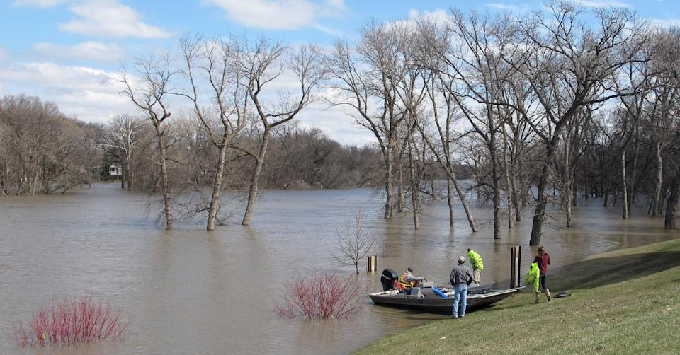 In this April 30, 2013 photo, members of the United States Geological Survey prepare to launch a boat on the Red River in Fargo, N.D., so a USGA hydrologist can take stream flow measurements. Even with reams of data, forecasting a flood is still an imprecise science. (AP Photo/Dave Kolpack)