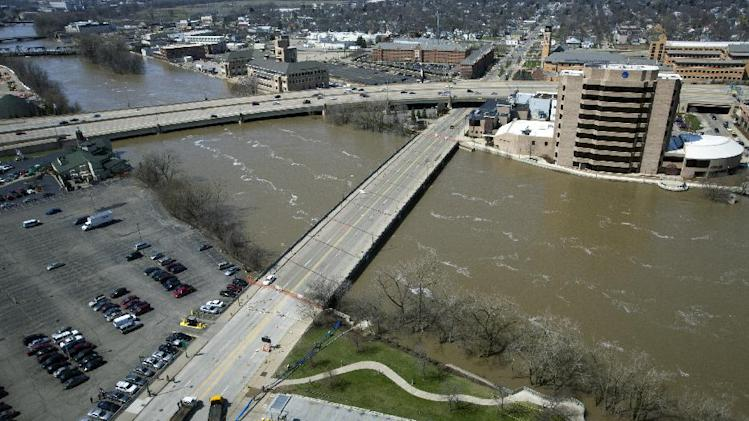 The Fulton Street bridge over the flooded Grand River, right, as pictured from the 27th floor of Plaza Towers in Grand Rapids, Mich., Sunday, April 21, 2013. The U.S. 131 bridge is pictured to the left. The Fulton Street bridge has been closed and the Plaza Towers evacuated because of flood waters. Grand Rapids Mayor George Heartwell declared a state of emergency as the flooding Grand River poured into the basements of several hotels and other downtown buildings. (AP Photo/The Grand Rapids Press, Cory Morse)