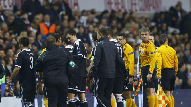 Players and officials leave the pitch due to several pitch invasions by spectators during the Europa League soccer match between Tottenham Hotspur and Partizan Belgrade in London