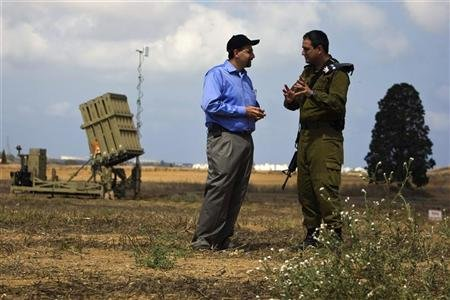 U.S ambassador to Israel Shapiro listens to an Israeli army colonel as they stand next to a launcher in a field near the southern city of Ashkelon
