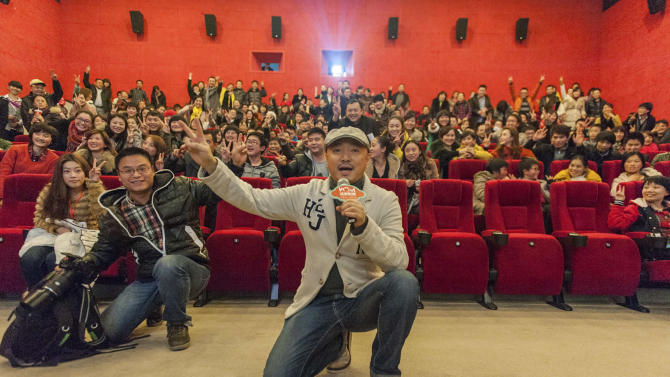 """In this Dec. 20, 2012 photo, movie director and actor Xu Zheng, center, speaks with fans at a movie theatre to promote his latest movie """"Lost in Thailand"""" in southwestern China's Chongqing city. The low-budget, domestically produced comedy has unexpectedly become the highest-grossing Chinese film to date. (AP Photo)  CHINA OUT"""