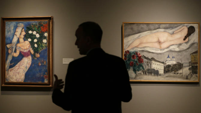"""In this photo taken Wednesday, Feb. 13, 2013, museum curator Olivier Meslay talks about paintings by artist Marc Chagall included in the """"Chagall: Beyond Color,"""" exhibit during a preview at the Dallas Museum of Art in Dallas. This will be the only U.S. venue to host the exhibit that opens to the public on Sunday. (AP Photo/LM Otero)"""
