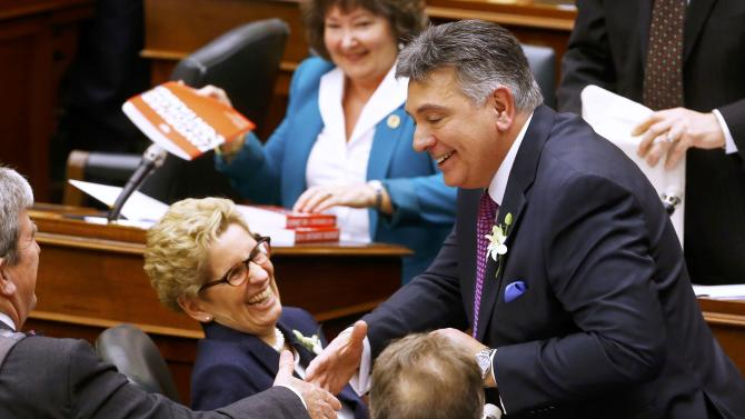Ontario Finance Minister Charles Sousa accepts congratulations along with Ontario Premier Kathleen Wynne after he delivered the provincial budget at Queens Park in Toronto