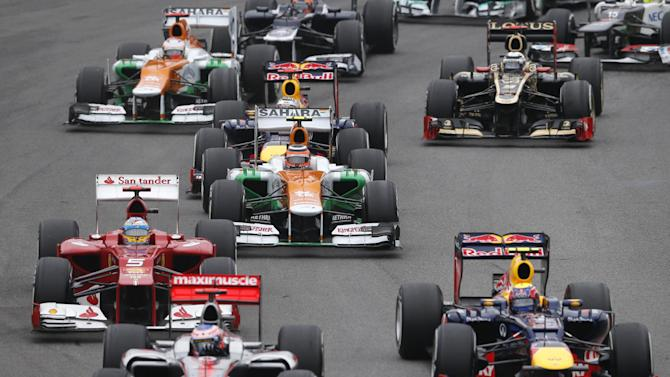 Red Bull driver Mark Webber of Australia, right, McLaren Mercedes driver Jenson Button of Britain, front second from  left, and Ferrari driver Fernando Alonso of Spain (5), at left,  steer their cars during the Formula One Brazilian Grand Prix at the Interlagos race track in Sao Paulo, Brazil, Sunday, Nov. 25, 2012. (AP Photo/Silvia Izquierdo)