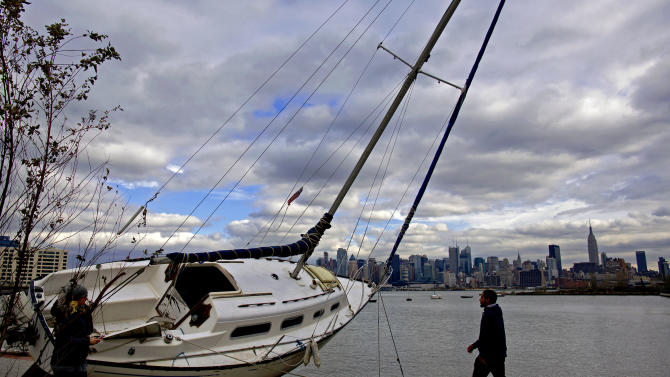 The Manhattan skyline is the backdrop for a sailboat tossed onto the shore in Hoboken, N.J. Wednesday, Oct. 31, 2012 in the wake of superstorm Sandy. Parts of Hoboken are still covered in standing water. Sandy, the storm that made landfall Monday, caused multiple fatalities, halted mass transit and cut power to more than 6 million homes and businesses. (AP Photo/Craig Ruttle)