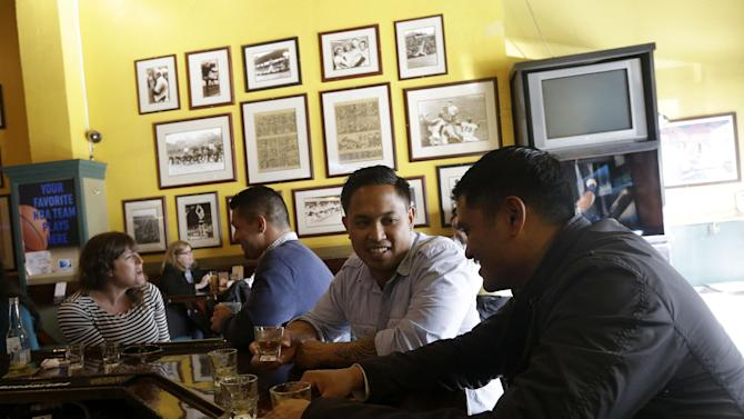Armand Gaerlan, right, and Chris Torio have a drink at Steff's Sports Bar in San Francisco, Wednesday, April 3, 2013. Across California, 2 a.m. is the witching hour for bartenders to issue the last call for drinks. But a proposed state law would give nightlife loving cities the option of allowing their bars and clubs to keep serving drinks for two more hours. (AP Photo/Jeff Chiu)