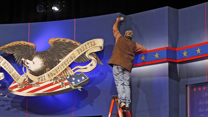 A stagehand uses a lint roller to clean the background on the stage at the Magness Arena at the University of Denver, Tuesday, Oct. 2, 2012, where the first presidential debate between President Barack Obama and Republican presidential candidate Mitt Romney is scheduled for Oct. 3.  (AP Photo/Ed Andrieski)