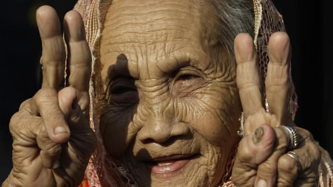 A Filipino Muslim woman flashes peace signs after hearing news of the signing of a preliminary peace pact between the government and the nation's largest Muslim rebel group during a rally outside the gates of the Malacanang presidential palace in Manila, Philippines, on Monday Oct. 15, 2012. Muslim rebels and the Philippine government overcame decades of bitter hostilities and took their first tentative step toward ending one of Asia's longest-running insurgencies with the ceremonial signing of a preliminary peace pact Monday that both sides said presented both a hope and a challenge. (AP Photo/Aaron Favila)