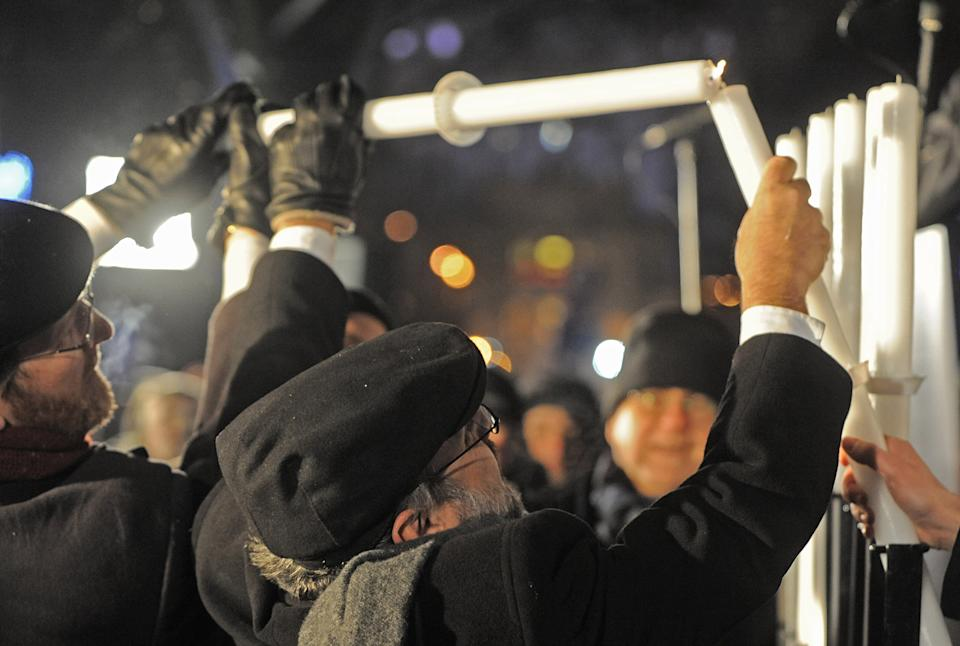 Poland's chief rabbi Michael Schudrich, center, lights the first candle celebrating the beginning of Hanukkah, the Jewish festival of lights, on Grzybowski square in Warsaw, Poland, Saturday, Dec. 8, 2012. (AP Photo/Alik Keplicz)