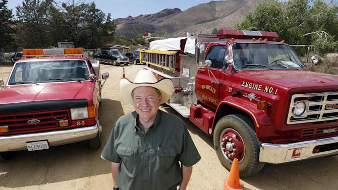 In this Aug. 29, 2013 photo, Leo Grilloposes with two of his firefighting rigs at his DELTA (Dedication & Everlasting Love to Animals) Rescue complex in Acton, Calif. Nearly 35 years ago, Grillo thought he could get people to stop dumping dogs and cats in the forests and deserts of Southern California. After more than three decades, there is no end to the number of animals he finds discarded on the side of the road. Delta Rescue is now the largest no-kill, care-for-life sanctuary in the nation for abandoned pets, home to some 1,500 dogs, cats and horses with 50 employees, a state-of-the-art hospital with full-time veterinarian, and his own fire department. (AP Photo/Reed Saxon)