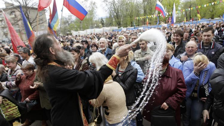 An Ukrainian Orthodox priest sprays holy water on pro-Russian supporters at the seized office of the SBU state security service in Luhansk