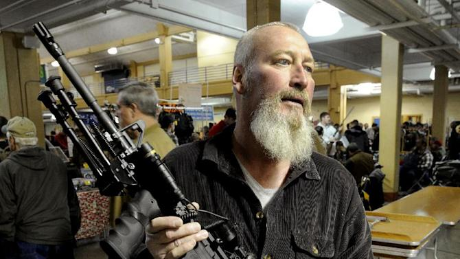 This Dec. 28, 2012 file photo shows Roy Shanks with a Smith and Wesson-made variation of the AR-15 rifle that he purchased at the RK Gun Show in the Smokies in Knoxville, Tenn. President Barack Obama's proposed ban on new assaults weapons and large-capacity magazines has struck a nerve among rural lawmen and lawmakers, with many vowing to ignore any new restrictions _ and even try to stop federal officials from enforcing gun policy in their jurisdictions. (AP Photo/Knoxville News Sentinel, Michael Patrick)