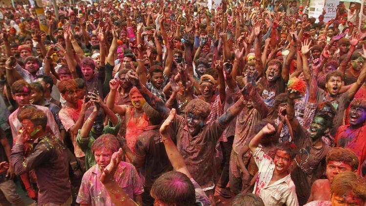 People daubed in colours cheer as they celebrate Holi in Guwahati